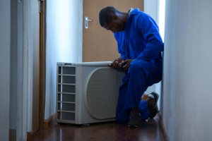 Technician wearing blue overalls and kneeling while inspecting AC unit on floor with brown door in background